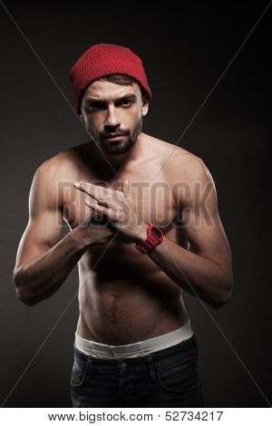 Young fit man in a menacing attitude smashing the closed fist against the palm of the hand in a back background