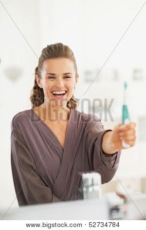 Happy Young Woman Showing Toothbrush