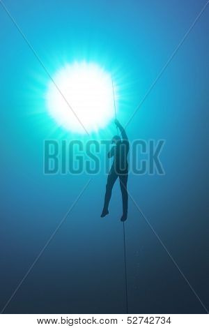 Freediver Holding A Rope And His Breath In The Water