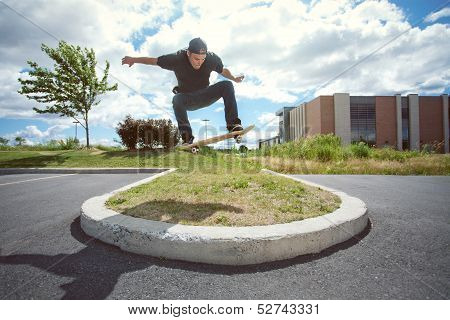 Skateboarder Doing A Ollie Over A Grass Section