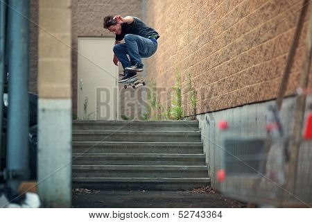 Skateboarder Doing A Kickflip Down The Stairs