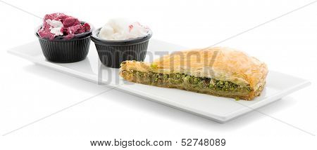 Slice of baklava with pistachio and ice cream isolated on white background