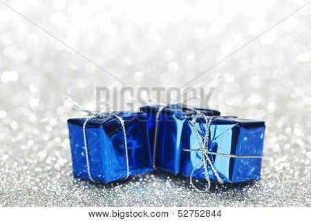 Blue boxes with christmas gifts on shiny silver background