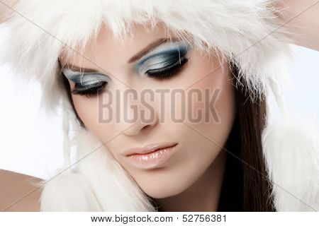 Closeup photo of beautiful female face with professional makeup and fur cap, looking down.
