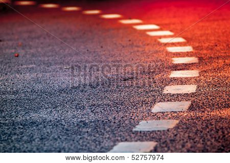 Turning Asphalt Road With Marking Lines And Bright Red Reflections
