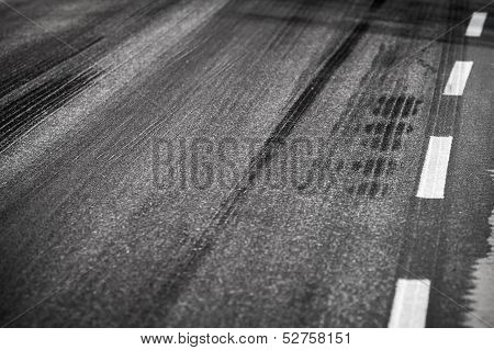Asphalt Road With Marking Lines And Tire Tracks. Close Up Photo With Selective Focus