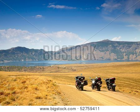 Landscape with mountain lake and three motorbikes