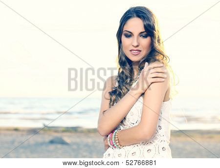 Portrait of a beautiful girl with curly hair and white dress who is posing outdoors