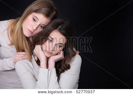 Young woman trying to comfort her friend