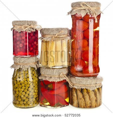 Collection tower of many glass bottles with preserved food isolated on white background