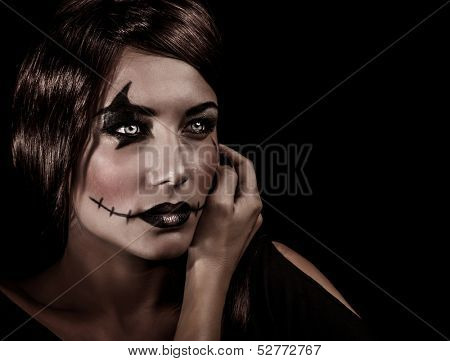 Closeup portrait of beautiful female with aggresive makeup for Halloween party, scary autumnal party celebration, mystery concept