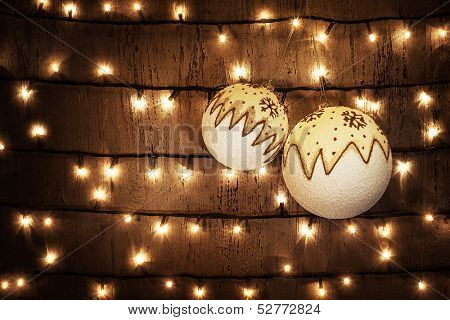 Photo of beautiful Christmastime ornament, two decorative white Christmas balls hanging on the door decorated with glowing garland at home, xmas bubbles on dark brown grunge background
