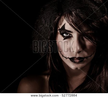 Terrifying witch portrait isolated on black background, attractive woman with scary makeup, Halloween party, horror concept