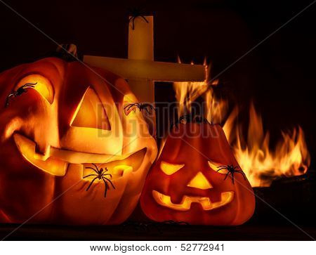 Scary Halloween night, aggresive burning fire on cemetery near cross, terrible carved pumpkin face laughing, holiday party, horror concept