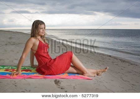 Attractive Girl Sitting On A Towel, Looking To The Sea