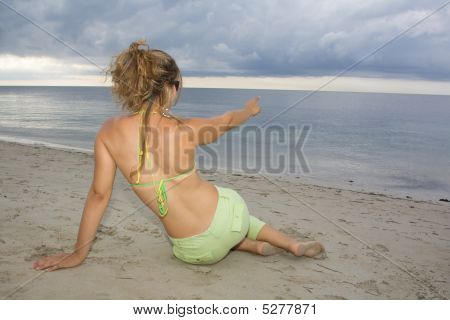 Blond Girl Pointing To The Sea On Sunset