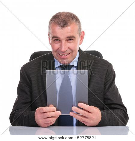 business man sitting at his desk and holding a transparent pannel while smiling for the camera. on a white background
