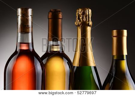 Closeup of four wine bottles backlit with a light to dark gray background. A Blush, Chardonnay, Sauvignon Blanc and Champagne bottles are shown from shoulder up. Horizontal Format.