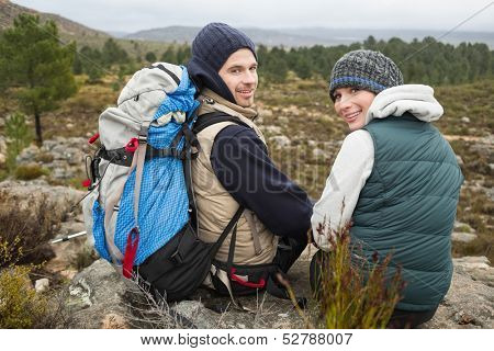 Rear view portrait of a smiling couple with backpack relaxing while on a hike