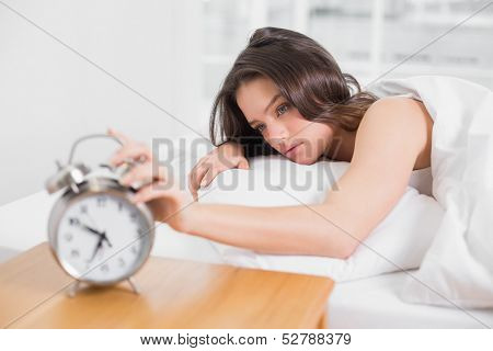 Sleepy young woman in bed extending hand to alarm clock at home