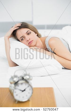 Gorgeous thinking woman lying on her bed under the cover in the bedroom