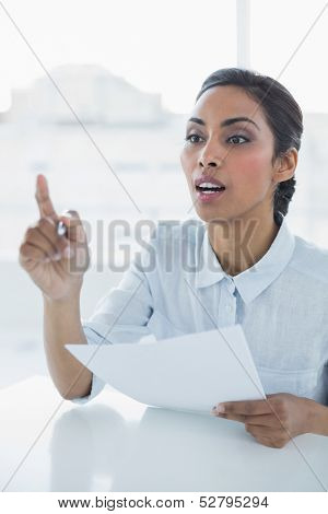 Classy businesswoman sitting at her desk in bright office