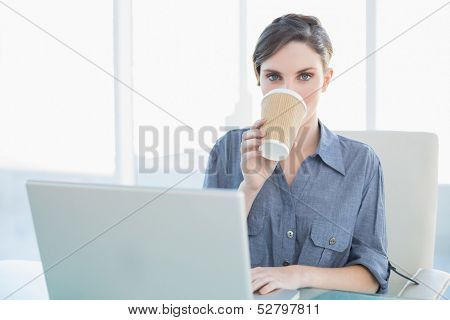 Gorgeous young businesswoman drinking from disposable cup sitting at her desk