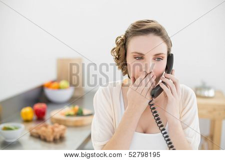 Astonished young woman phoning with her telephone in her kitchen at home