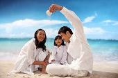 foto of three life  - A shot of Family of three playing at beach