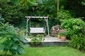 stock photo of greenery  - Back garden and patio with furniture in a British home