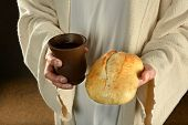 stock photo of gospel  - Jesus hands holding bread and wine over dark background - JPG