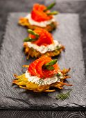 stock photo of buffet lunch  - Potato pancakes topped with smoked salmon - JPG