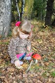 pic of overcoats  - Pretty little girl with pink bows in overcoat sits next red toadstool in forest - JPG
