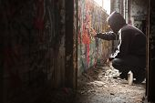 stock photo of graffiti  - Illegal Young man Spraying black paint on a Graffiti wall - JPG