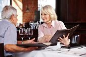 Two senior people with menu in restaurant for lunch