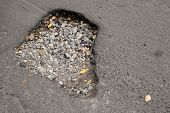 Pothole With Gravel On Damaged Urban Asphalt Road