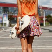 stock photo of thighs  - Funky Girl with skateboard walking on street - JPG
