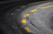stock photo of track field  - Abstract turning road background with tires track and yellow striped road marking on dark asphalt