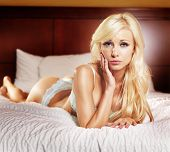 stock photo of skinny girl  - sexy blonde girl with large breasts in lingerie laying on bed - JPG