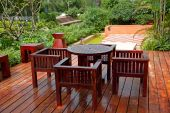 pic of wooden table  - House patio with wooden table and chairs in a backyard - JPG
