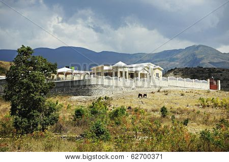 A beautiful yellow home surrounded by rock walls and fencing near the base of Haiti's mountains.  Two horses graze nearby.