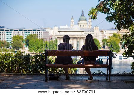 Two Girls On A Bench Watching At Szechenyi Chain Bridge