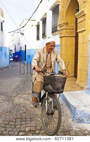 RABAT, MOROCCO - OCTOBER 15 2013: Arab man is biking in the medina of Rabat Morocco
