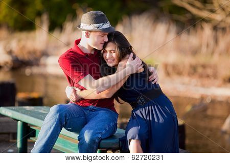 Young Interracial Couple Sitting Together On Dock Over Lake