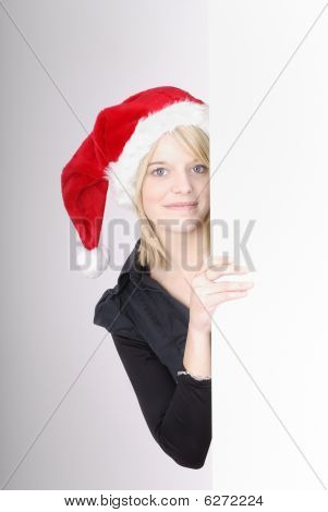 Beautiful Young Blond Woman With Santa Head Behind An Ad Space