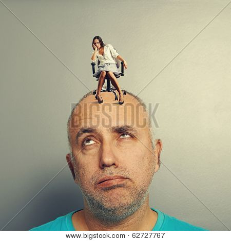 tired man with small doleful woman over grey background