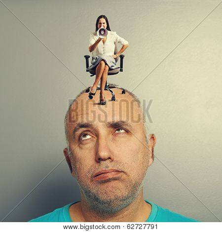 tired man and angry woman on his head over grey background