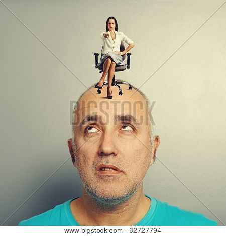 strict young woman pointing and sitting on tired man over grey background