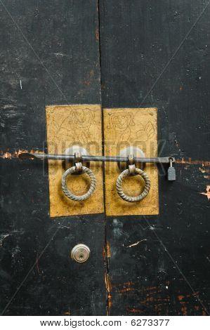Chinese Antique Door-handles On The Black Old Wooden Door.
