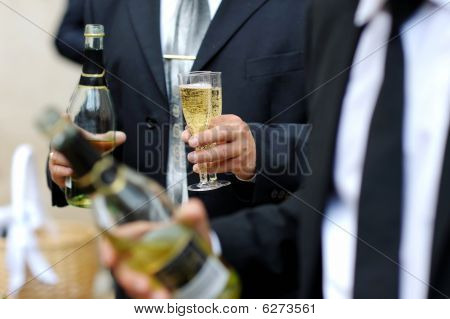 Groom Holding Bottle And Glasses Of Champagne